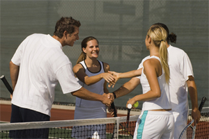 Photo of two couples shaking hands over the net after a tennis match